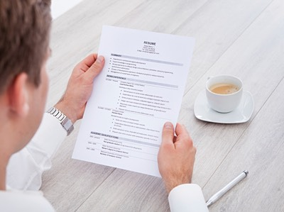 Businessman Reading Resume With Tea Cup On Desk